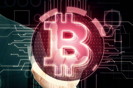 E-business and cryptocurrency concept. Hand using lowing red bitcoin interface in blurry dark background. Double exposure  Zdjęcie Seryjne