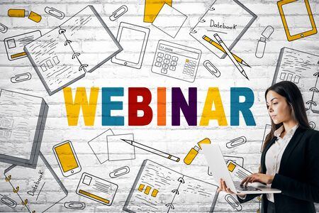Attractive european businesswoman using laptop with creative colorful webinar sketch on white brick wall background. Web, internet and workshop concept