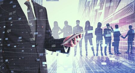 Businessman using tablet with abstract crowd silhouettes on city background with bid data. Success and meeting concept. Multiexposure 版權商用圖片