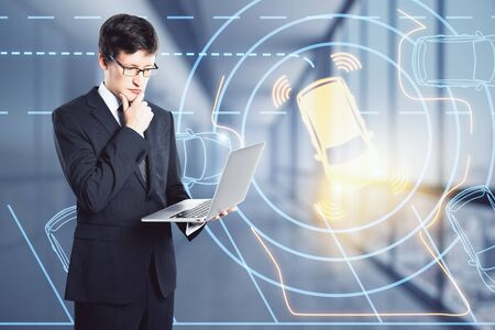 Attractive young european businessman using laptop with abstract car interface. Transport and innovation concept. Double exposure