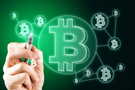 E-business and cryptocurrency concept. Hand using lowing green bitcoin interface in blurry dark wallpaper.