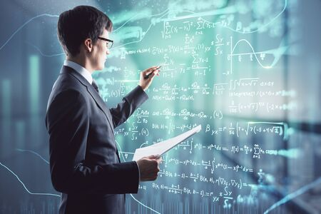 Attractive young european businessman with mathematical formulas hologram on blurry office interior background. Complex and math concept. Multiexposure