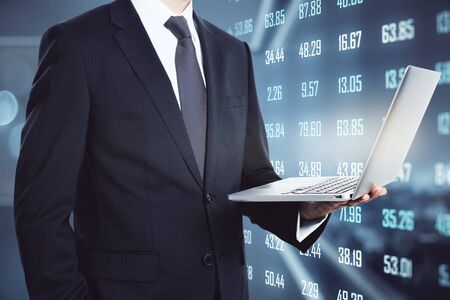 Businessman with laptop and abstract digits hologram on blurry office interior background. Technology and big data concept. Multiexposure
