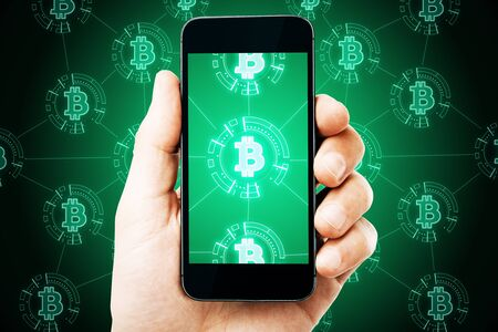 Cryptography and mobile banking concept. Close up of hand holding tablet with glowing bitcoin hologram on screen 版權商用圖片