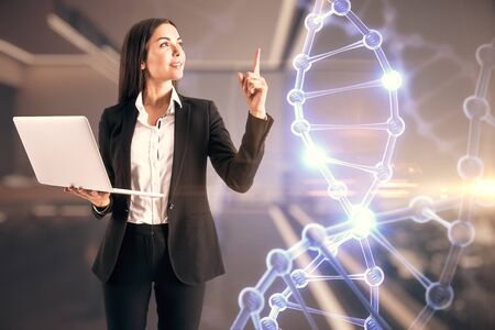 Attractive young european businesswoman with laptop and abstract cogwheel hologram on blurry office interior background. Technology and medicine concept. Double exposure 版權商用圖片
