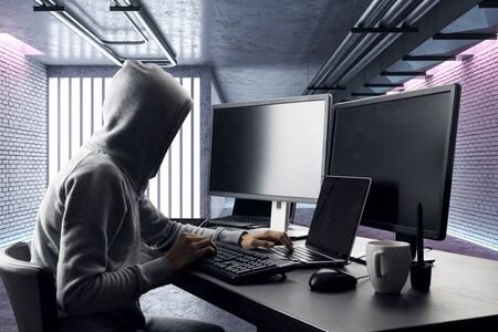 Side view of hacker at desktop with coffee cup using computers in modern interior. Hacking and malware concept