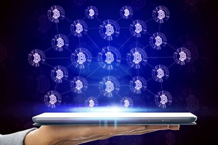 E-commerce and mobile banking concept. Close up of hand holding tablet with glowing bitcoin hologram on screen 版權商用圖片