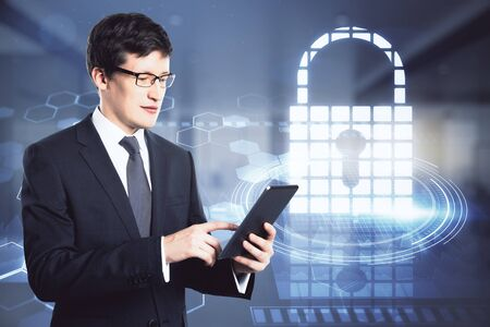 Attractive young european businessman with tablet and abstract digital padlock hologram on blurry office interior background. Technology and protection concept. Double exposure