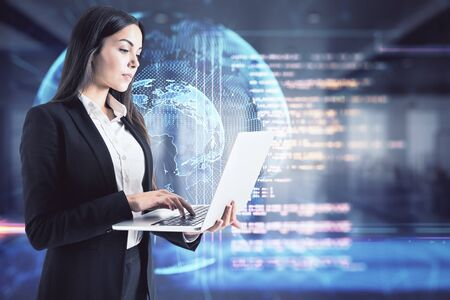 Attractive young european businesswoman with laptop and abstract globe hologram on blurry office interior background. Technology and global data concept. Multiexposure