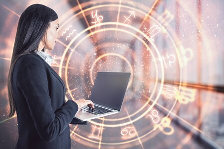 Attractive young european businesswoman with laptop and abstract zodiac sign hologram on blurry office interior background. Technology and astrology concept. Double exposure Stock Photo