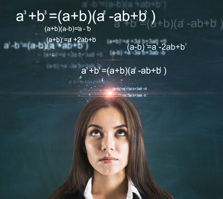 Portrait of attractive thoughtful young european businesswoman with glowing mathematical formulas on chalkboard background. Complex and algorithm concept