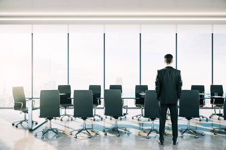 Businessman standing in Coworking meeting room interior with city view and daylight.