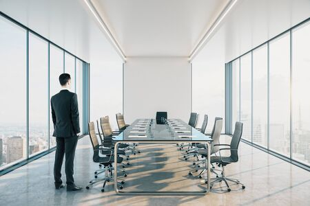 Businessman standing in modern meeting room interior with city view and daylight.