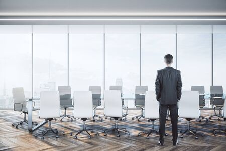 Businessman standing in luxury conference room interior with city view and daylight. Фото со стока