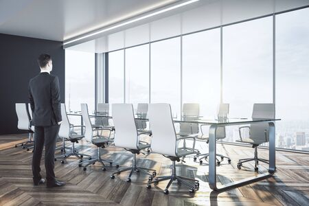 Businessman standing in luxury meeting room interior with city view and daylight.