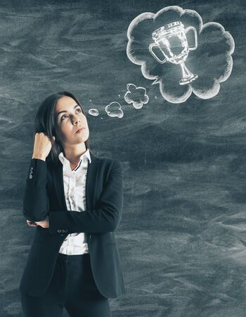 Thoughtful young european businesswoman thinking about trophy on blackboard wall background. Leadership and success concept