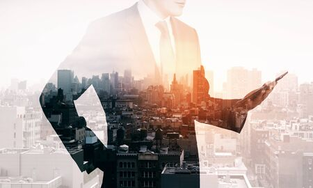 Businessman standing on blurry city background with tablet. Success and career concept. Multiexposure
