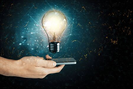 Businessman holding phone with light bulb representing artificial intelligence. Close up Banque d'images