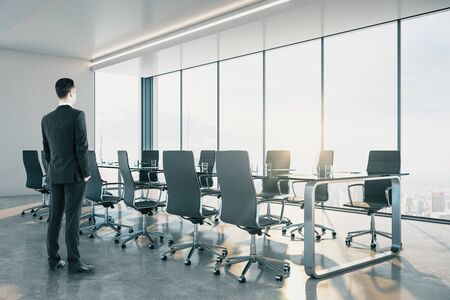 Businessman standing in contemporary meeting room interior with city view and daylight.