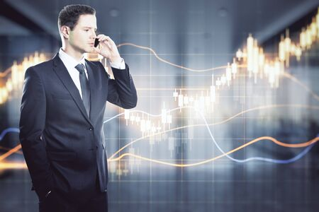 Finance and network concept. Portrait of attractive young european businessman on the phone with glowing forex chart on blurry office interior. Double exposure