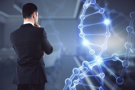 Medicine and science concept. Portrait of attractive young european businessman with glowing DNA hologram interface on blurry office interior. Multiexposure