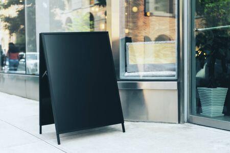 Leerer schwarzer Menüstand neben dem Caféeingang. Café- und Restaurantkonzept. Attrappe, Lehrmodell, Simulation