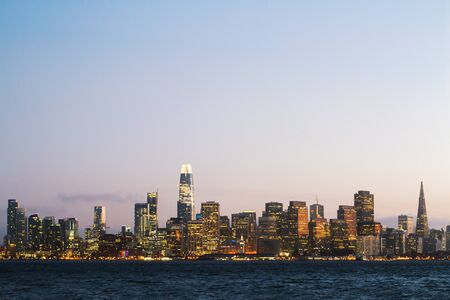 Modern waterfront San Francisco city skyline background with illuminated buildings at dawn. Urban architecture concept Standard-Bild