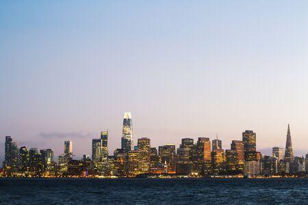 Moderner San Francisco Skyline-Hintergrund am Wasser mit beleuchteten Gebäuden im Morgengrauen. Urbanes Architekturkonzept