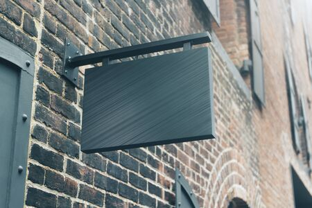 Empty black outdoor banner on brick wall. Commercial and ad concept. Mock up 版權商用圖片