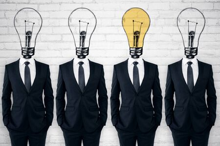 Row of  lightbulb headed businessmen standing in brick interior. Leadership and confidence concept