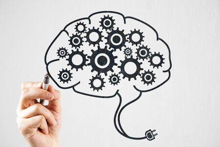 Hand drawing cogwheels in brain. Teamwork and mechanism concept.