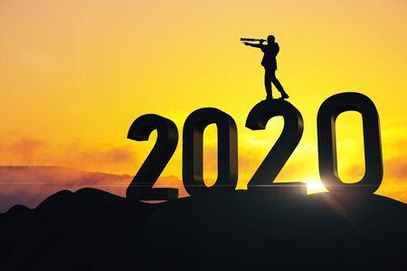 Uomo d'affari con telescopio in piedi sul testo del nuovo anno 2020 Successo e concetto di avvio.