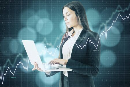 Businesswoman with laptop and stock data hologram. Trade and currency concept. Zdjęcie Seryjne
