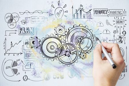 Businessman hand drawing cogwheel and business start up sketch on wall. Teamwork and startup concept. Stock fotó