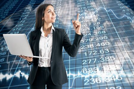 Businesswoman with laptop and stock data hologram on modern building background. Trade and currency concept.