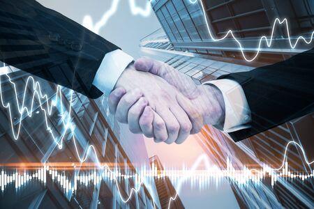 Businessmen handshake on blurry city background with forex chart. Teamwork and finance concept. Zdjęcie Seryjne
