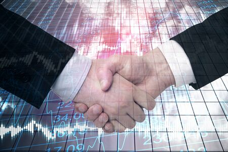 Businessmen handshake on building background with stock chart. Teamwork and finance concept.