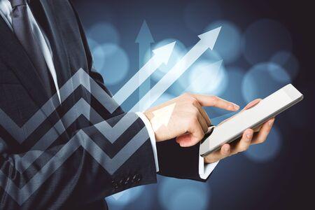 Businessman hand using tablet with arrow chart hologram. Analytics and trade concept. Zdjęcie Seryjne