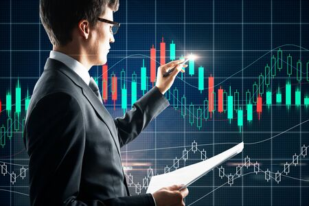 European businessman with document drwing forex chart hologram. Trade and currency concept