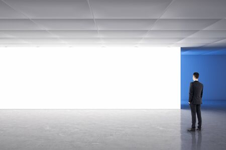 Businessman in gallery interior looking on empty billboard. Mock up, Imagens