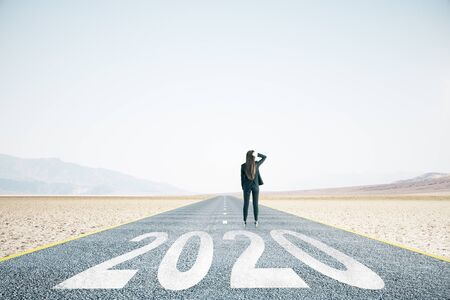 Businesswoman walking on road with drawing 2020 new year text.