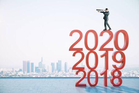 Businessman with telescope standing on 2020 new year text on buildings background. Success and startup concept. Stock Photo