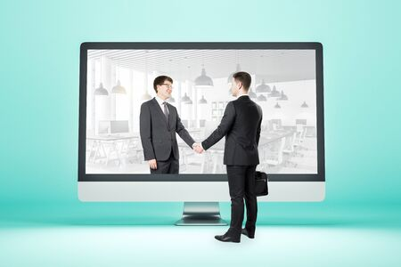 Computer screen on table with businessmen shaking hands. Partnership and success concept.