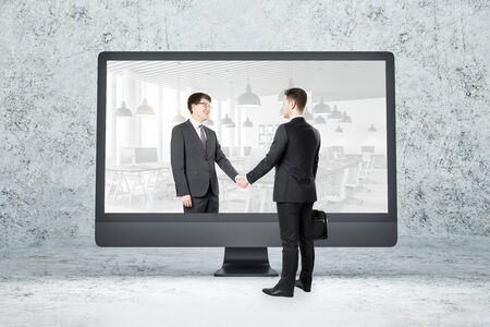 Computer monitor on table with businessmen shaking hands. Partnership and success concept. Stockfoto