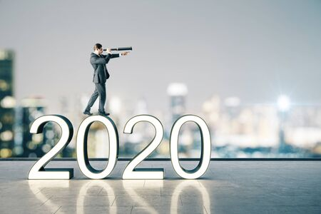 Businessman with telescope standing on white 2020 new year text on buildings background. Success and startup concept.