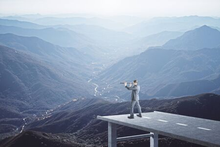 Businessman standing on end road and looking in telescope to mountain landscape. Success and startup concept. 版權商用圖片 - 135688684