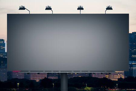 Tabellone per le affissioni nero vuoto sullo sfondo della città di notte. Annuncio pubblico e concetto di business. Modello