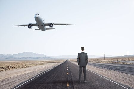 Businessman standing on road and passenger airplane flying in the blue sky. Travel and vacation concept