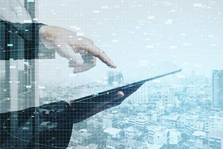 Businessman hand using tablet with stock report hologram on city background. Business and financial success concept.