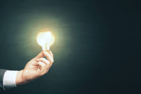 Hand holding light bulb on green background. Success and startup concept. Stok Fotoğraf